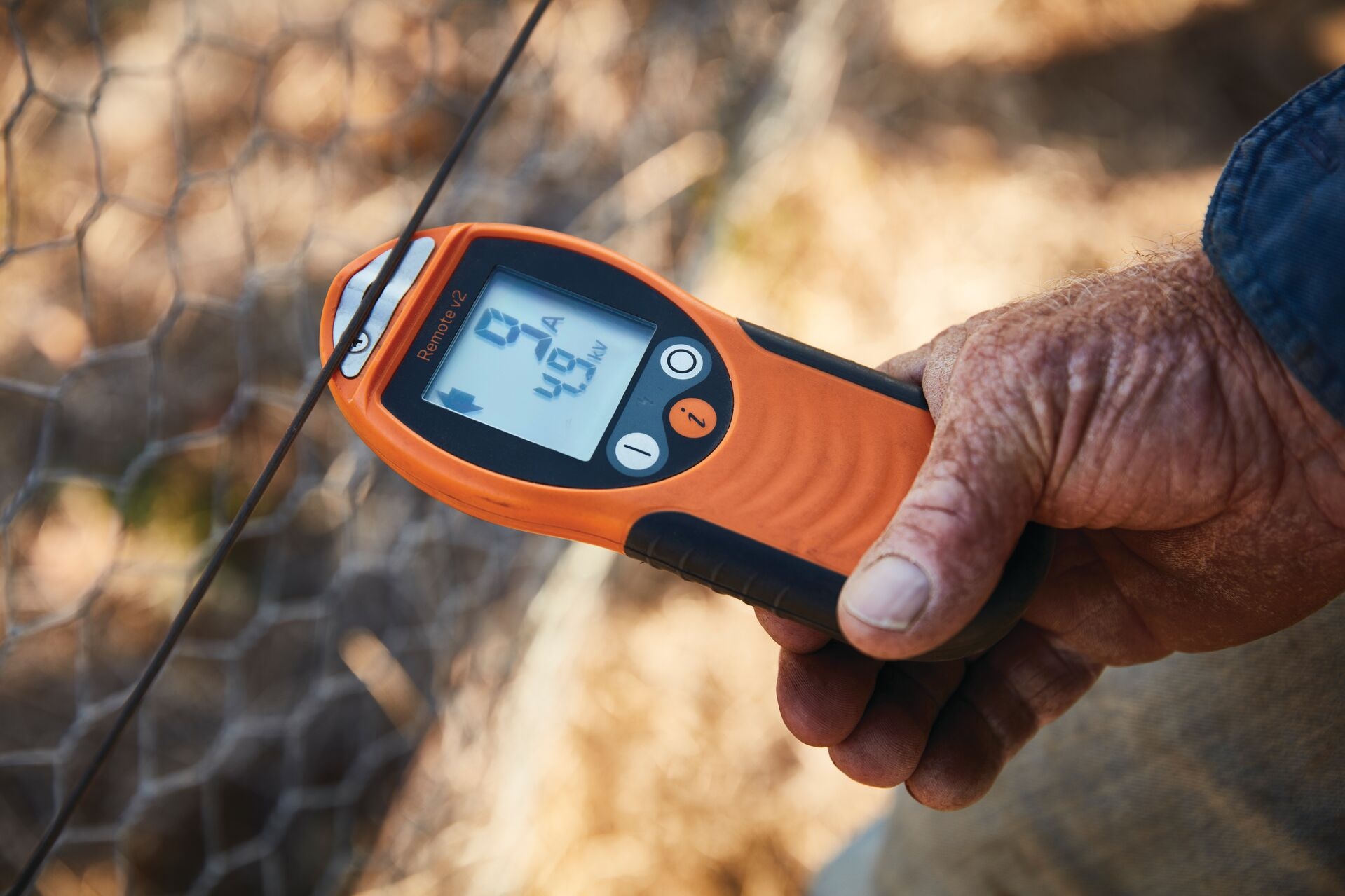 Gallagher i Series Remote Control and Fault Finder being used by farmer to test electric fence